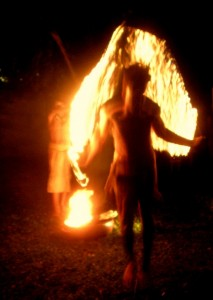A young man, clad only in a loin cloth, jump-ropes with a chain of fire.