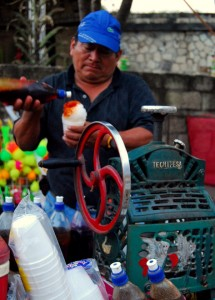 A local man adds sweet syrup to a cone of hand-shaved ice.