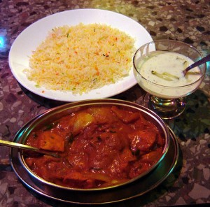 Chicken Tikka Jalfrezi, Pilau Rice, Cucumber Raita at The Aladin Restaurant in Brick Lane, London. Photo via Wikimedia Commons, by Fin Fahey.
