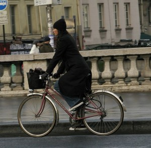 A woman on a bike in Paris. Photo via Wikimedia, by Ben_pcc.